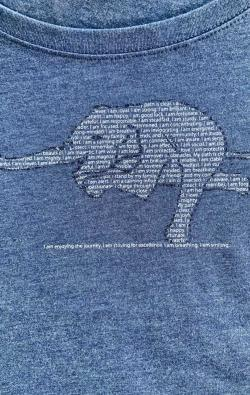closeup image of Think Possible Apparel's yoga elephant affirmations design screen printed on a navy shirt