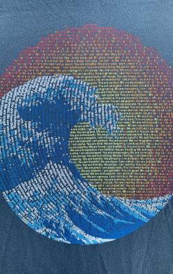 super closeup image of Think Possible Apparel's great wave yin yang design screen printed on a deep blue shirt