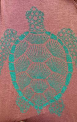 closeup image of Think Possible Apparel's turtle affirmations design screen printed on a mauve shirt
