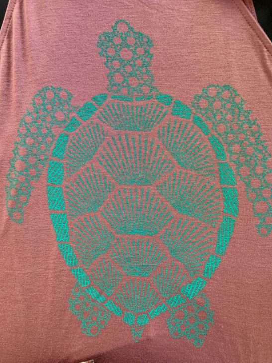 Our turtle design is made entirely from affirmations about the symbolism of the turtle and screen printed on a stylish high neck flowy tank - closeup product image