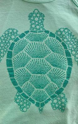 closeup image of Think Possible Apparel's turtle affirmations design screen printed on amint shirt