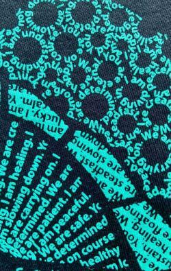 super closeup image of Think Possible Apparel's turtle affirmations design screen printed on a black shirt